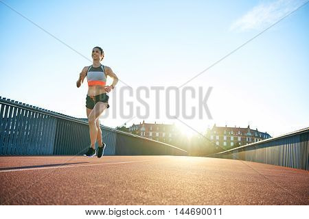 Low angle of sun behind single confident fit female athlete in shorts running along bridge with copy space in sky