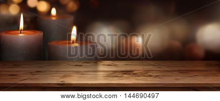 Wooden table with burning candles against a dark background