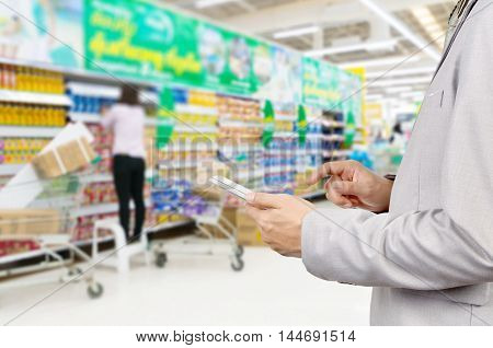 Hand Of Businessman Use Mobile Tablet In Supermarket