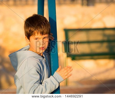 Adorable boy with green eyes playing in the playground. Beautiful sunny winter day