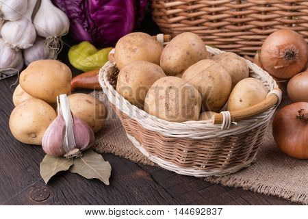 Vegetables in a basket on an old wooden table. Selective focus.
