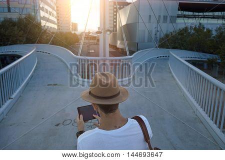Man On Pedestrian Bridge With Tablet