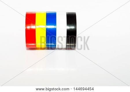 Multicolored insulating tapes roll on white background with reflections and soft shadows.