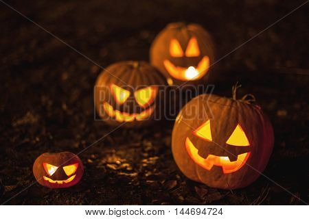 Halloween jack-o-lantern pumpkins on ground with brown autumn leaves