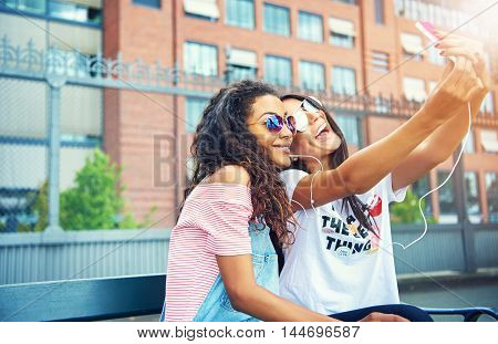Cute young female friends in sunglasses and short sleeved shirts taking selfies on bench near large brick building