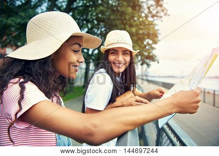 Woman in overalls and smiling reads a map while her happy friend stands nearby