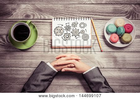 Top view of businesswoman hands and her sketch book on table