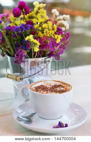 cup of cappuccino and bouquet of wildflowers in summer terrace of cafe