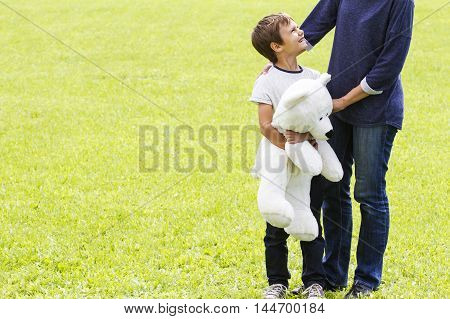 Mom hugging her boy. Child have a teddy bear. Outdoor. Family concept