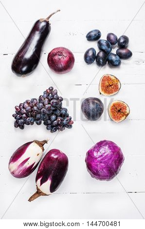Collection of fresh purple fruit and vegetables on wooden background.
