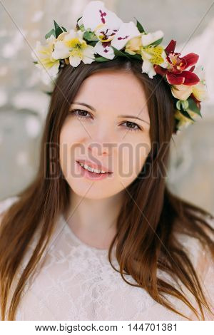 Close-up portrait - brunette woman in floral wreath of orchids and delicate white dress.