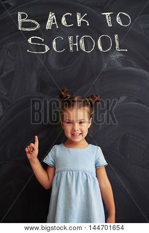Pretty girl in a casual light-denim dress with two buns smiling and holding finger up against school blackboard