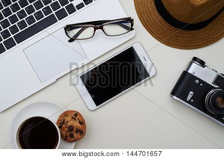 Top view of cup of coffee with cookie, laptop, eyeglasses, smartphone, photo camera and hat on white surface of the table