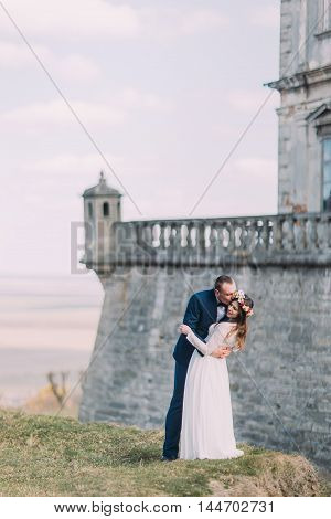 Newlywed bride and groom kiss near beautiful baroque fortress wall. Magnificent sky view at background.