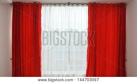 Window of hotel room with red curtains open