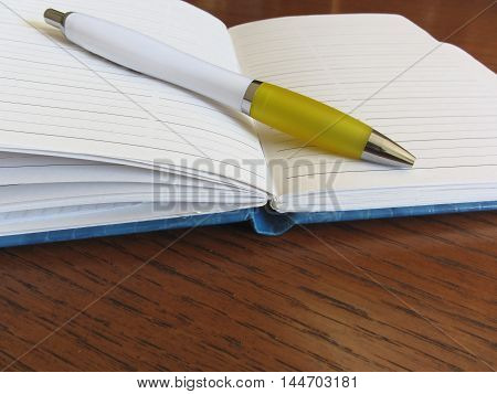 Opened blank lined notebook with pen on wooden table