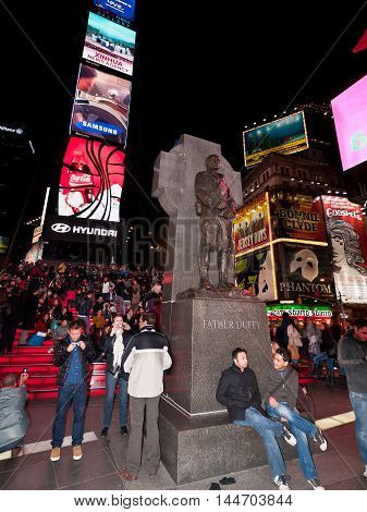 New York USA - November 20 2011: Crowds of people sitting on benches and on the red steps or walking past the red steps above the TKTS booths behind the statue of Father Duffy at Times Square in the evening with large neons in the background. With the bri