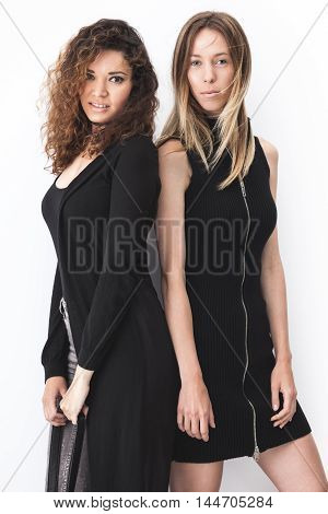 Two modern fashion girls posing near white wall