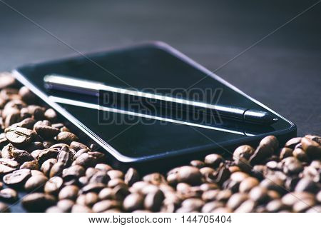 coffee beans. Stylus pen on a smart phone and raw coffee Background. Energy. Raw coffee beans. Harvesting. Natural background. Lifestyle. Coffee break in a morning. Mobile. Technology