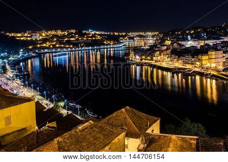 Porto, Portugal. View of the Old Town. Night cityscape. Douro river with the traditional Rabelo boats in the night the light of lanterns. Night photographing slow shutter speeds.