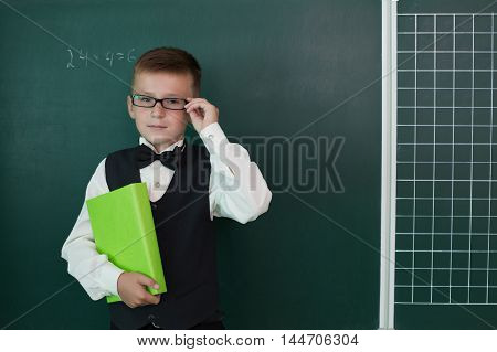 Happy pupil with glasses holding schoolbook near rhe schoolboard