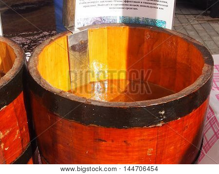 Fresh, odorous honey in lime kegs is on sale at a fair