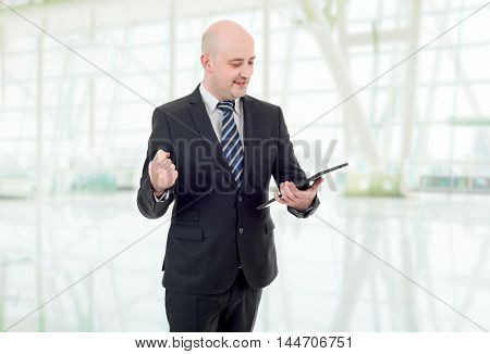 businessman winning, using touch pad of tablet pc, at the office