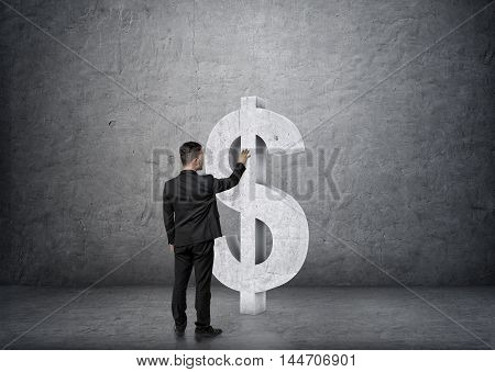 Back view of businessman touching big concrete dollar sign on concrete wall backgound. Economy and finance. Money and profit. Successful lifestyle.