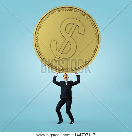 Businessman stands and holding heavy, big golden coin on blue background. Financial success. Money and wealth. Signs and symbols.