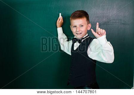 Schoolboy near the school board writing with chalk