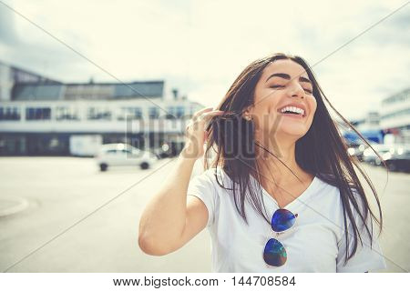 Cute woman with sunglasses on shirt adjusts her long brown hair as it waves in air at large parking lot outdoors