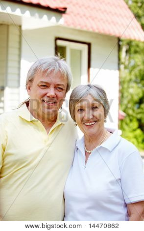 Portrait of happy senior couple embracing each other and looking at camera on sunny day