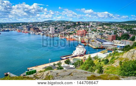 Panoramic views with bright blue summer day sky with puffy clouds over the harbor and city of St. John's NewFoundland, Canada.