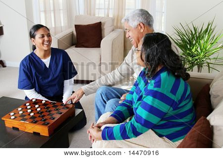 Home health care worker and an elderly couple playing game
