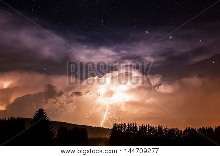 Beautiful view of dramatic dark stormy sky and lightning over small willage at night. Germany, Bavaria.
