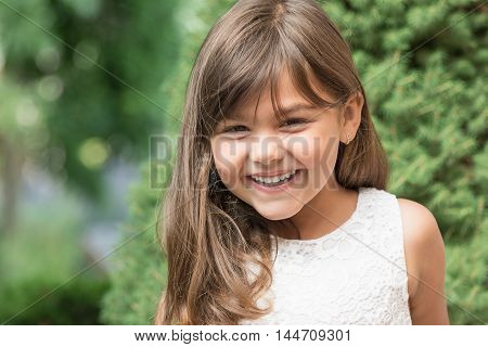 Portrait of laughing attractive little girl outdoors.