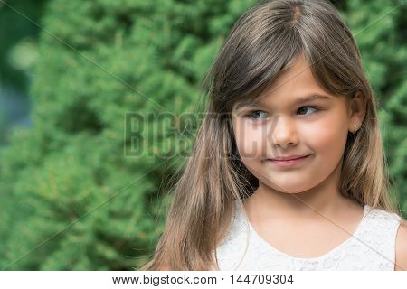 Portrait of little girl outdoors. Girl is looking at the sideways.