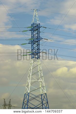 Electricity. Pylon against blue cloudy sky. High-voltage tower.