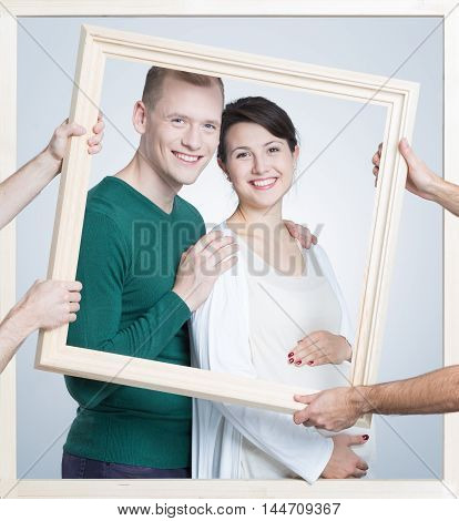 Shot of a future young parents in a frame holded by somebody's hands