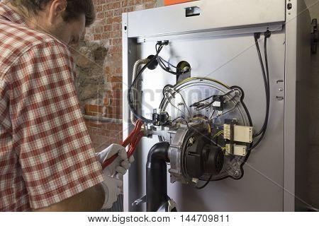 Plumber Repairing A Condensing Boiler In The Boiler Room