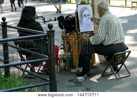 NEW YORK UNITED STATES - AUGUST 25TH 2016: An artist sketches a woman in Central Park on summer afternoon
