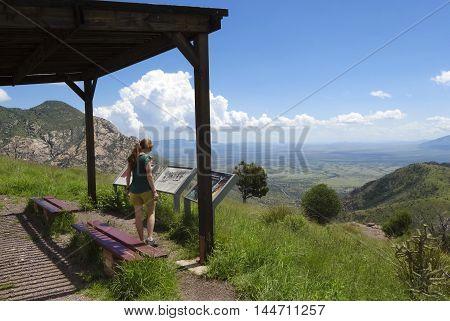 SIERRA VISTA, ARIZONA, AUGUST 21. Coronado Peak on August 21, 2016, near Sierra Vista, Arizona. A woman reads the placards on top of Coronado Peak in the Huachuca Mountains near Sierra Vista Arizona.