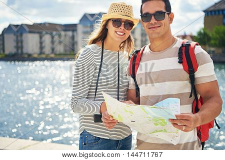 Couple of happy tourists on summer vacation standing on a waterfront promenade in sunglasses in the hot sunshine smiling and holding a map