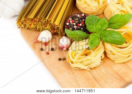 Italian pasta fettuccine nest with fresh basil leaves on white background