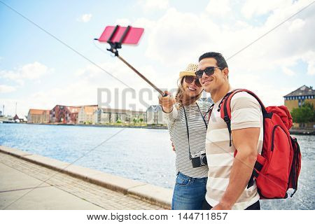 Happy young tourists posing for a selfie standing close together on an waterfront promenade with the attractive trendy young woman holding the stick
