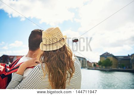 Young couple on vacation taking a selfie as they stand overlooking a waterfront town view from behind looking towards the mobile phone on the end of the stick