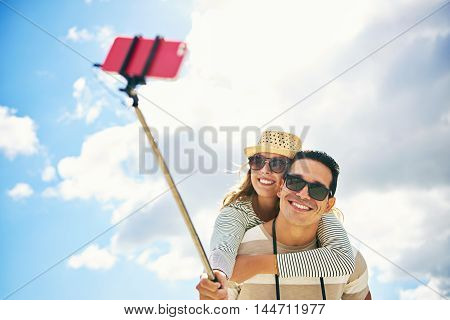 Young woman enjoying a piggy back ride clasping the shoulders of a handsome young man as they pose for a selfie grinning happily at the camera