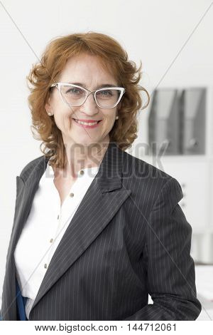 Portrait of a smiling middle-aged businesswoman wearing grey formal jacket and modern glasses
