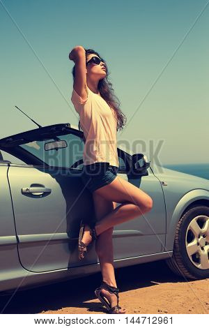 Beautiful Woman Posing In Short On Blue Sea And Sky Background Near Cabriolet Car In Sun Glasses. To