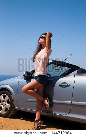 Beautiful Woman Posing In Short On Blue Sea And Sky Background Near Cabriolet Car In Sun Glasses